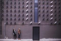 ściana z rzędami kamer skierownych na ulicę. Dołem przechodzą dwie kobiety spglądające na kamery.